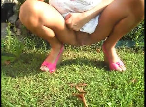 Red-hot doll pissing in grass