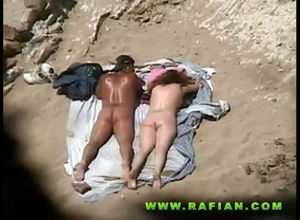 Naturist duo plumbs on beach in..